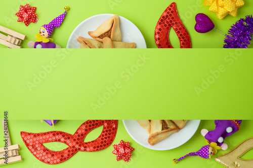 Jewish holiday Purim background with carnival mask and hamantaschen cookies.