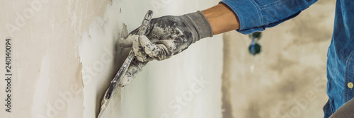 Cuadros en Lienzo master is applying white putty on a wall and smearing by putty knife in a room o