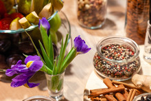 Closeup Snacks, Purple Irises, Fresh And Dried Fruits, Red, White And Black Pepper Mix In Glass Bowl, Cinnamon Sticks, Nuts. Concept Degustation Premium Alcohol At Opening Of Shoes Store