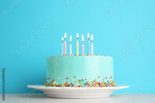 Fresh delicious birthday cake with candles on table against color background