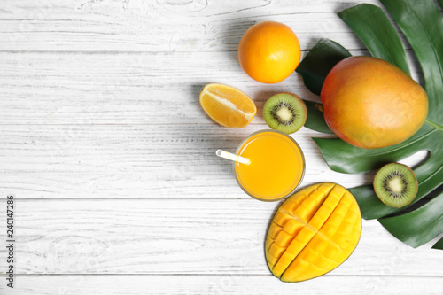Glass of tasty mango juice and fresh fruits on wooden table, flat lay. Space for text