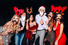 Six Young Funny Friends, Four Girls And Two Boys While Celebrating Christmas. Group Of Friends At Club Having Fun. New Year's Party