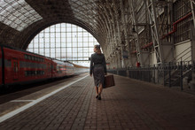 Girl With A Suitcase In Hand And In Retro Clothes Walking Down The Station