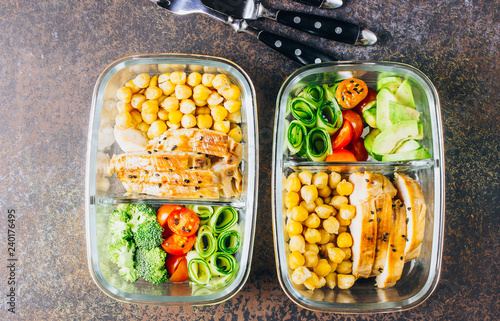 Healthy meal prep containers chicken and fresh vegetables.