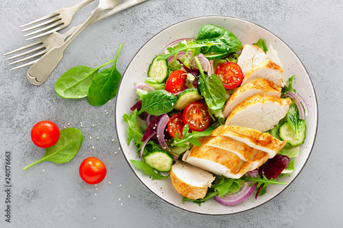 Foto op Aluminium Kip Grilled chicken breast, fillet and fresh vegetable salad of lettuce, arugula, spinach, cucumber and tomato. Healthy lunch menu. Diet food. Top view