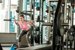 Young girl in gym healthy lifestyle squatting with barbell concentrated