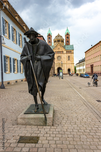 Leinwand Poster Statue of a pilgrim on his way to santiago de compostela in front of Speyer Cath
