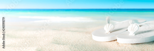 Fototapeta White Shells And Sandals On Sandy Beach With Tropical Water And Blue Sky - Beach