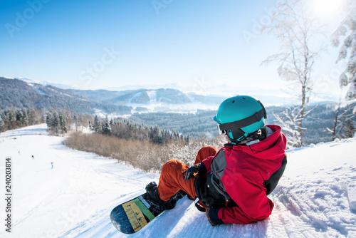 Stickers pour portes Glisse hiver Rearview shot of a relaxed man snowboarder lying on the snowy slope enjoying stunning mountains view resting after riding at the winter resort copyspace landscape recreational lifestyle activity