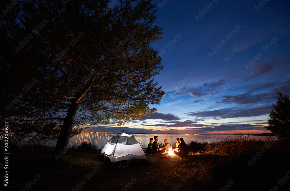 Fototapety, obrazy: Group of five tourists having a rest on lake shore around campfire near tent under big tree and blue evening sky with first stars at sunset. Tourism, friendship camping and beauty of nature concept.