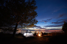 Group Of Five Tourists Having A Rest On Lake Shore Around Campfire Near Tent Under Big Tree And Blue Evening Sky With First Stars At Sunset. Tourism, Friendship Camping And Beauty Of Nature Concept.