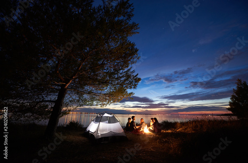 Group of five tourists having a rest on lake shore around campfire near tent under big tree and blue evening sky with first stars at sunset Canvas Print