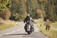 Back View Of Biker In Black Leather Jacket And Helmet Riding Motorcycle Along Twisty Road On Blurred Background Of Dense Green Forest Trees On Bright Sunny Summer Day. Active Lifestyle And Traveling.