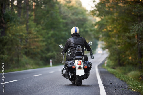 Back view of biker in black leather jacket and white helmet riding motorbike along hilly road between tall green trees Canvas Print