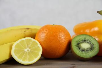 Zdrowa dieta - owoce i warzywa - pomarańcze, kwi, cytryna i banan na drewnianej skrzynce