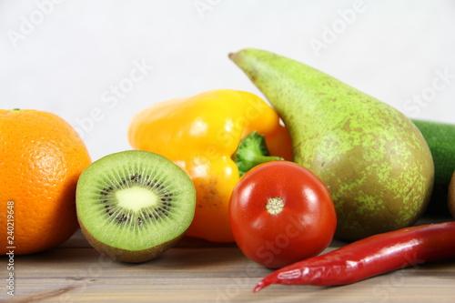 Zdrowa żywność - owoce i warzywa na drwenianej podstawie i jasnym tle