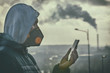 Man wearing a real anti-smog face mask and checking current air pollution with smart phone app