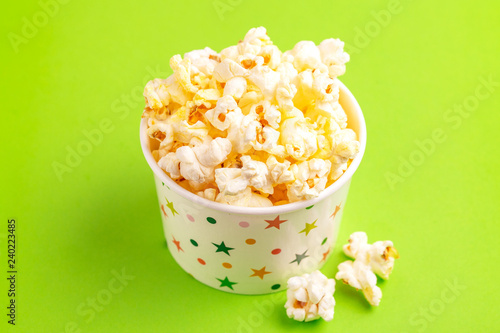 Photo  Tasty salty popcorn in paper cup on bright green backgraund