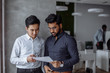 canvas print picture - Mix raced couple of male business partners planning next sales period. Indian and Korean male colleagues in formal shirts and studying documents in the big office room. Business concept