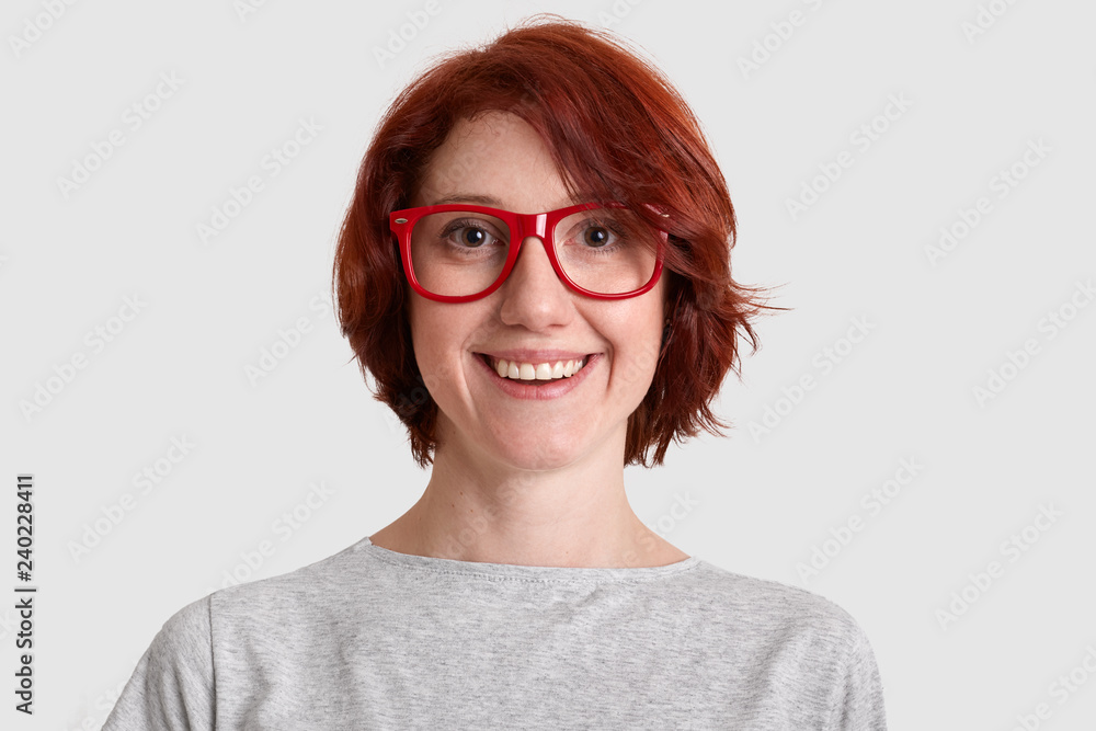 Fototapeta Close up shot of smiling glad woman with short hairstyle, wears red rimed spectacles, dressed casually, isolated over white background, expresses positive feelings. People and beauty concept.