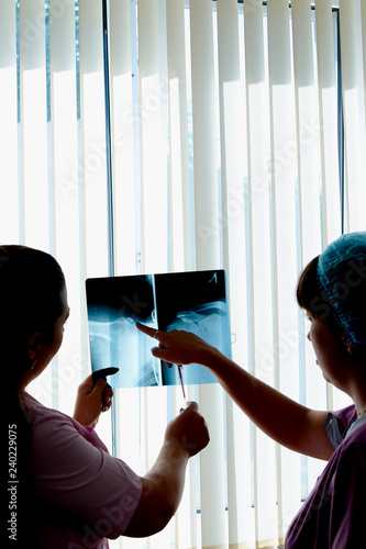 Photo  Female doctor and laboratory assistant look and discuss x-ray image and radiograph at hospital