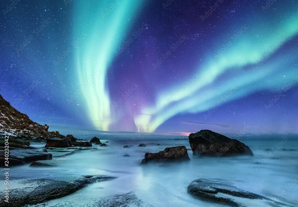 Aurora borealis on the Lofoten islands, Norway. Night sky with polar lights. Night winter landscape with aurora and reflection on the water surface. Natural background in the Norway