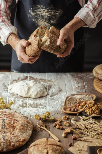 Fotografía  Man breaking off piece of rustic rye bread, standing at table with dough in flou