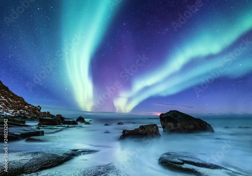 Poster Aurore polaire Aurora borealis on the Lofoten islands, Norway. Night sky with polar lights. Night winter landscape with aurora and reflection on the water surface. Natural background in the Norway