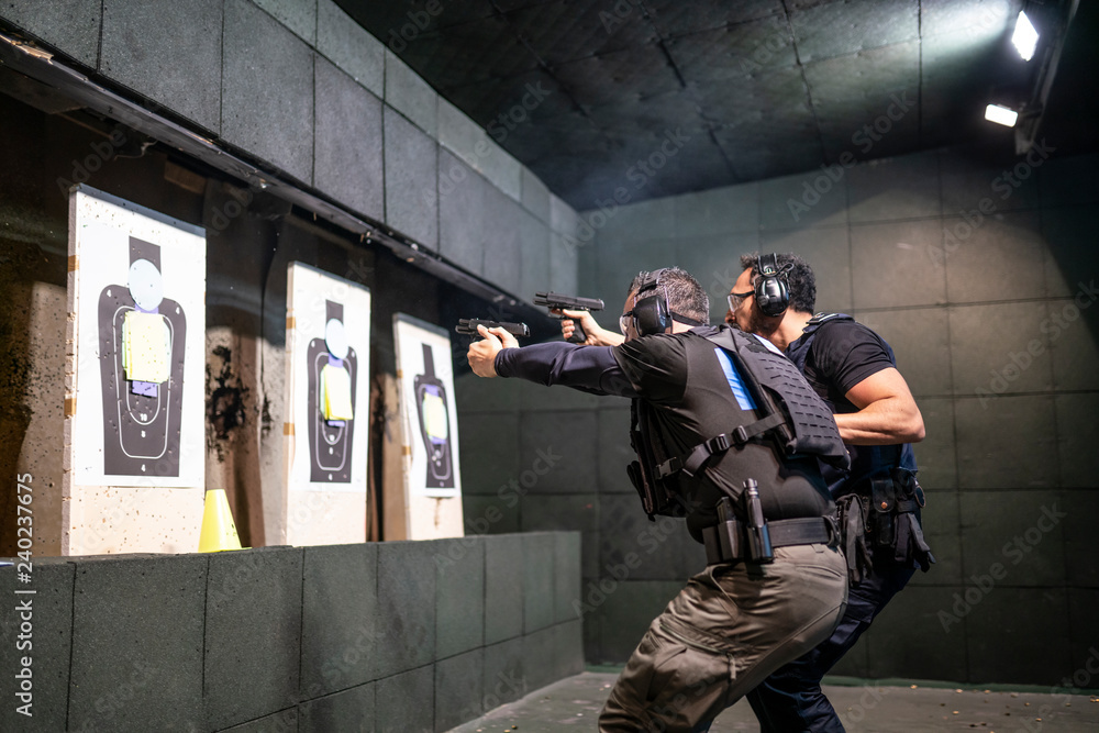 Fototapeta Police training in shooting gallery with short weapon.