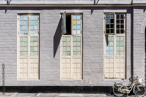 Photo Painted wooden wall with windows and a bicycle of a historic building in the center of Copenhagen, Denmark