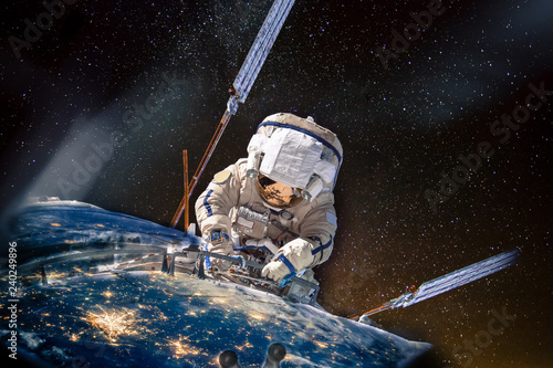 Giant astronaut repairman clings to the planet earth with visible night lights of cities in an open space. Conceptual collage, elements of the image furnished by NASA.