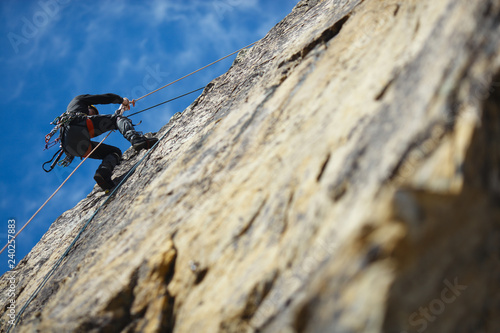 Fotografiet  The climber is hanging on a safety rope on a rock wall.