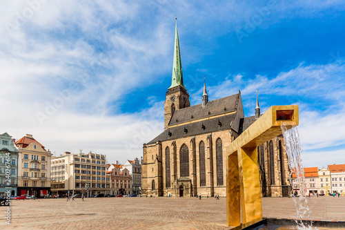 Foto op Plexiglas Historisch geb. St. Bartholomew's Cathedral in the main square of Plzen with a fountain on the foreground against blue sky and clouds sunny day. Czech Republic, Pilsen. Famous landmark in Czech Republic, Bohemia.