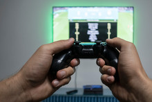 Man Playing Video Game. Hands Holding Console Controller. Football Or Soccer Game On The Television. Widescreen Tv Hangs On The Wall
