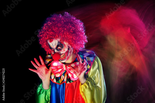 Low key picture of a horror clown looking to the camera with scary smile