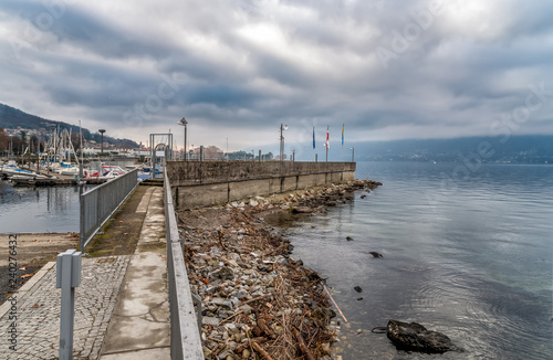 Valokuvatapetti New Harbor of Luino on the Lake Maggiore in cloudy day, province of Varese, Ital