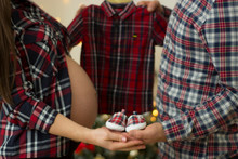 Future Parents Holding Hands And A Pair Of Little Shoes And A Boy Shirt Over Christmas Background. Concept Of Parents-To-Be.
