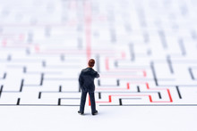 Miniature People, Businessman In The Labyrinth Or Maze Figuring Out The Way Out. Business Concept, Finding Solution, Strategic, And Business Opportunity.