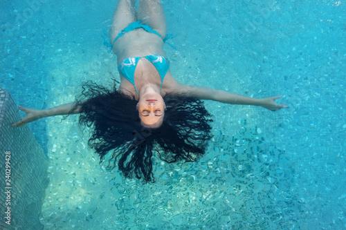 Fototapeta  schöne reife Frau im besten Alter mit dunklen Locken im blauen Bikini im Sonnenl