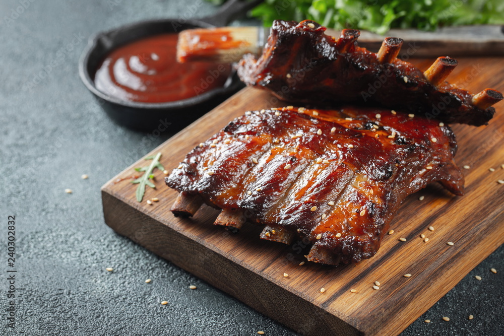 Fototapety, obrazy: Closeup of pork ribs grilled with BBQ sauce and caramelized in honey. Tasty snack to beer on a wooden Board for filing on dark concrete background
