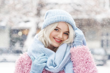 Close Up Outdoor Portrait Of Young Beautiful Happy Smiling Lady Wearing Stylish Winter Light Blue Beanie Hat, Scarf, Gloves, Pink Faux Fur Coat, Posing In Street