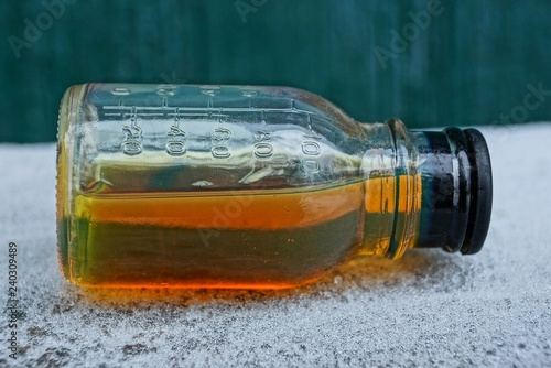 Fotografía  brown liquid from machine oil in a glass bottle on white snow on a green backgro