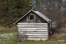 Old Log Cabin Storage Building On The Edge Of A Forest In Winter