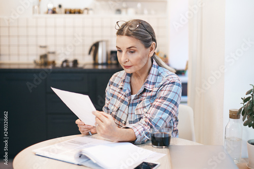 Fotomural Serious mature European housewife looking through domestic finances in kitchen while having morning coffee