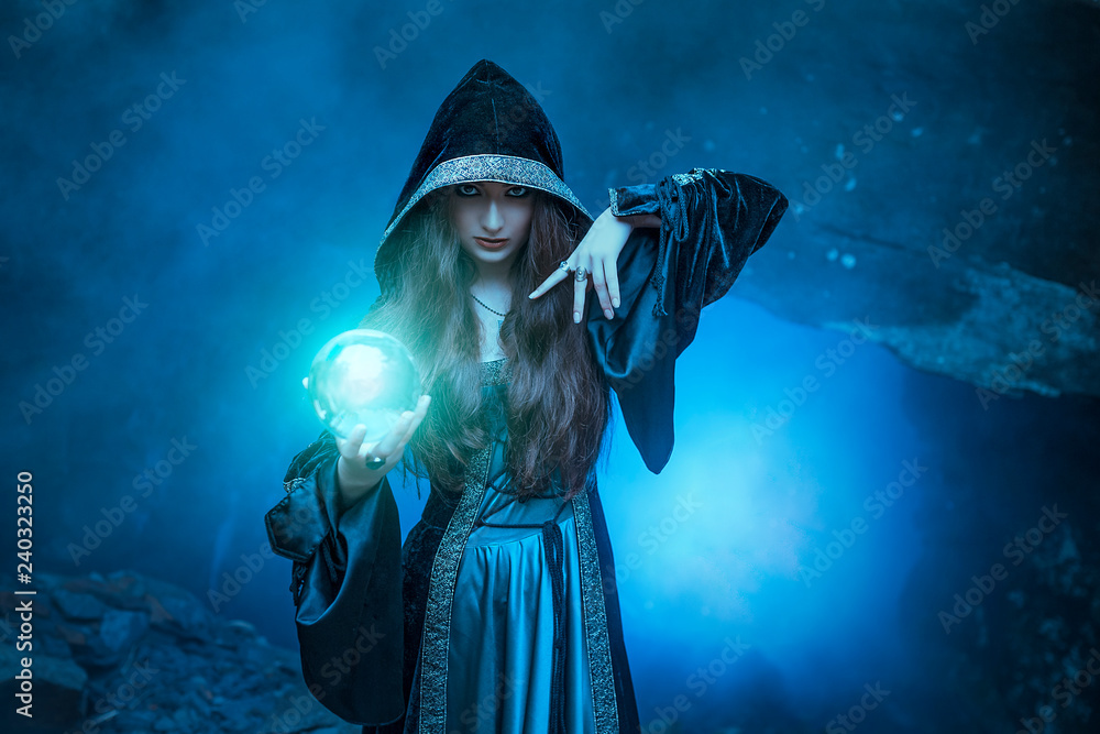 Fototapeta The witch with magic ball in her hands causes a spirits