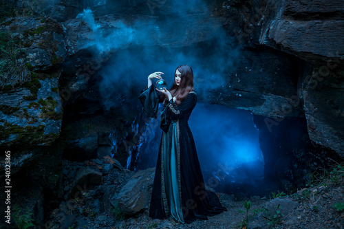 Fotografie, Obraz  The witch with magic ball in her hands causes a spirits
