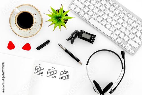 Fototapeta musician work set with guitar neck, keyboard, coffee and headphones white table background top view obraz na płótnie