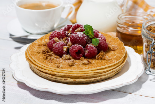 traditional sweet pancakes with fresh raspberries for breakfast on wooden table