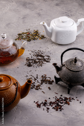 A variety of teapots with tea on a gray textured background. The concept of tea drinking.