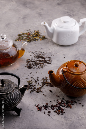A variety of teapots with tea on a gray textured background and a scattering of tea leaves. The concept of tea drinking.